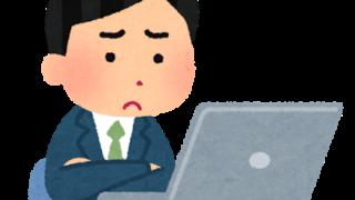 パソコンを見つめながら悩む男性
