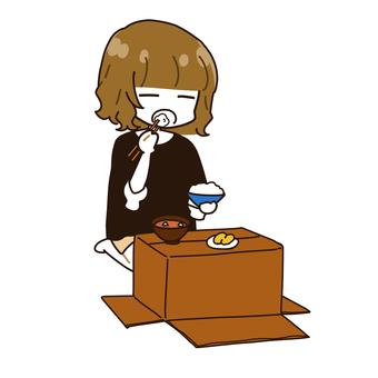 段ボール机でご飯を食べる女性