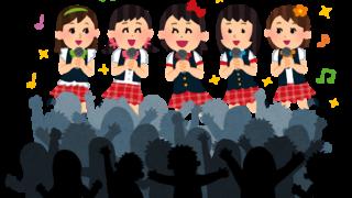 観客の前で歌う女性アイドルグループ