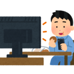 ながらスマホで一人でテレビを観ている男性