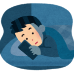 寝る前に布団でスマホを見ている男性