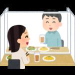 アクリル板ごしに食事する男女